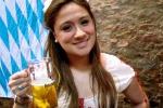 Giovani donne incostumi tradizionali trasportano fiumi di birra agliospiti assetati