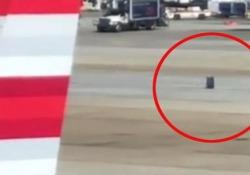 E rotola, e rotola, e rotola: la valigia spazzata via dal vento sulla pista dell'aeroporto