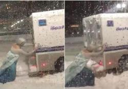 Uomo vestito da Elsa spinge il camioncino della polizia bloccato nella neve