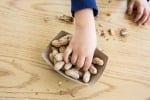 Le mani di un bambino che sta mangiando delle noccioline