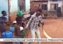 Sul set di Wakaliwood le Waka Stars cantano e suonano (per finta) reggendo bottiglie di plastica come microfoni e pentole come tamburi