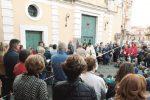 I fedeli portano le sedie da casa per la messa, dopo l'incendio in chiesa a Trecastagni