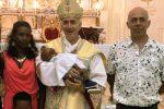 Monsignor Antonio Staglianò, vescovo di Noto, con in braccio il bimbo eritreo battezzato