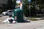 Cassonetto circondato dai rifiuti in via Restivo