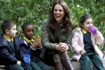 Britain's Kate, the Duchess of Cambridge sits on a log with children during a visit to the Sayers Croft Forest School and Wildlife Garden, in London, Tuesday Oct. 2, 2018. (Peter Nicholls/Pool Photo via AP)