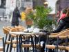 Una donna seduta ad un tavolino di un bar consuma un drink