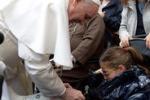 La foto. Papa Francesco firma il gesso di una bimba